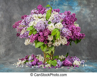 Lilac in a vase on the table. Dramatic light.