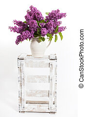 lilacs and lilies on a wooden crate