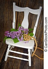 lilacs on white wood chair