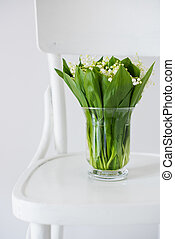lilies of the valley in vase on a rustic chair