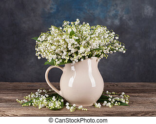 Lilies of the valley in vase on old board