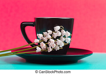 lilies of the valley on a black cup with a saucer.Bright background red and green color