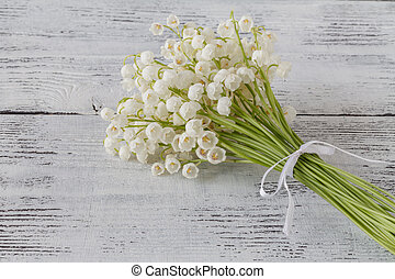 lilies of the valley on a white wooden background
