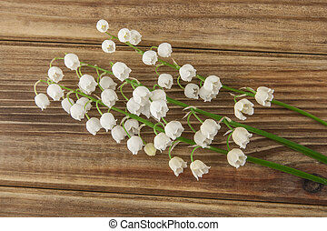 Lilies of the valley on a wooden background