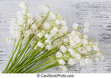 Lilies of the valley on wooden textured background