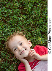 lille dreng, kigge kamera hos, liggende, på, grønnes græs