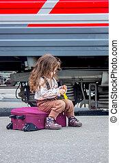 lille pige, siddende, hos, kuffert, på, jernbane station, hos, den, tog, på, baggrund.
