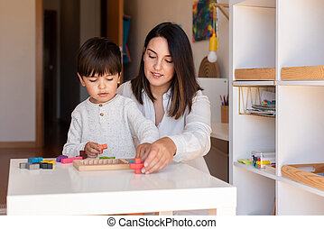 Lillte Kid playing with a tetris wood puzzle and mother or teacher help. Homeshooling. Learning Community. Montessori School