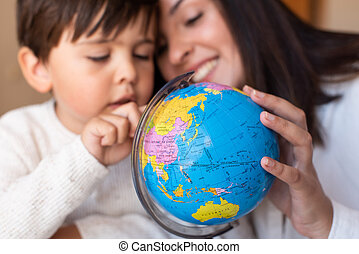 Preschooler Kid learing geography with a globe map and ...