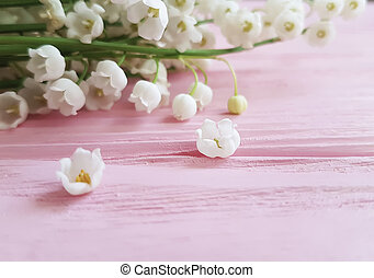 lily of the valley on a pink wooden background