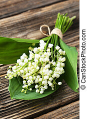 Lily of the Valley with leaves on brown wooden background