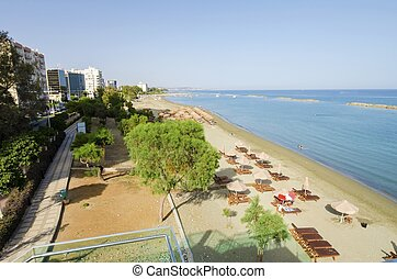 A summer view of the beach in Limassol city in Cyprus in Neapoli area, near the Olympic Residence. A view of the sand, the Mediterranean sea, tropical and exotic sun umbrellas and sunbeds and boardwalk path to the sea