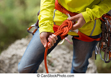 ?limber wearing safety harness making a eight rope knot