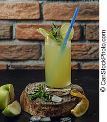 Lime and apple cocktail in glass with ice, mint leaves