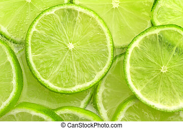 lime background - close up of sliced ??lime in sparkling ...
