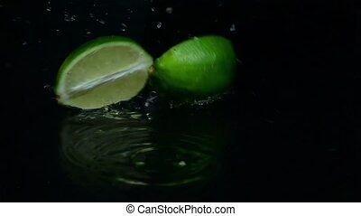 Lime cut into two slices falls. Black background. Slow motion