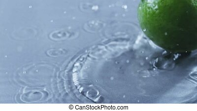 Lime falls into the water creating a spray. Slow motion 2k...