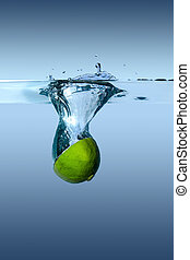 Lime falls into water on a blue background