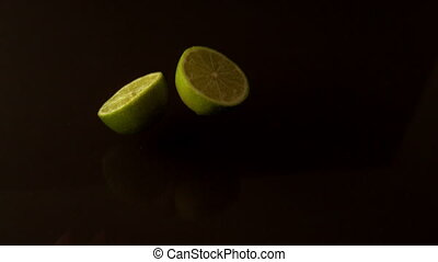 Lime halves dropping on wet black surface in slow motion