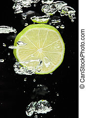 Lime (lemon) falling in water on black with air bubbles