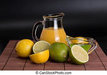 lime, lemon on bamboo mat on a dark background