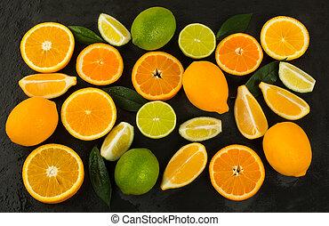 Lime, lemon, orange and tangerine on black background