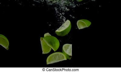 Lime pieces fall and float in water, black background -...