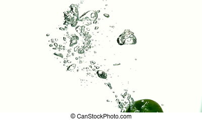 Lime plunging into water on white background in slow motion