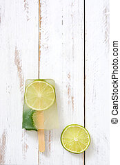 Lime popsicle on white wooden table