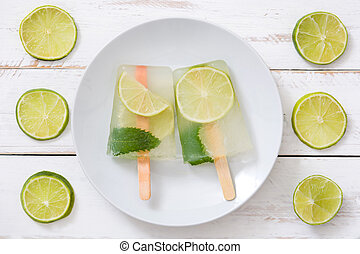 Lime popsicles on white wooden