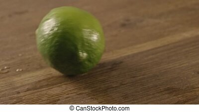 Lime rolls out on a black table - Green lime with drops of...