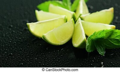 Lime segments with mint leaves - Closeup shot of layout of...