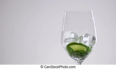 Lime slice and mint lies in a wine glass under ice cubes.