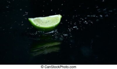 Lime slice falls into the water. Black background. Slow motion