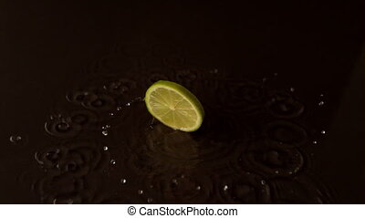 Lime slice spinning on wet black surface in slow motion