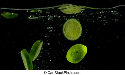 Lime slices fall and float in water, black background, slow...