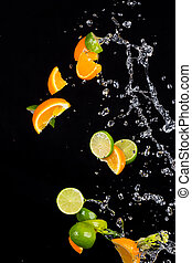 Limes and oranges with water splashes on black - Fresh limes...