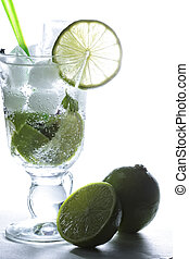 Limes at mojito cocktail glass in counter light