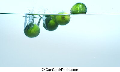 Limes dropping into water on blue background in slow motion.