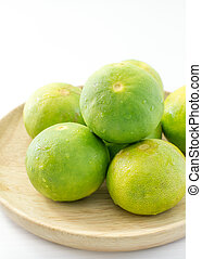 Limes on wooden dish on white background