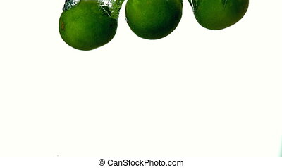 Limes plunging into water on white background in slow motion