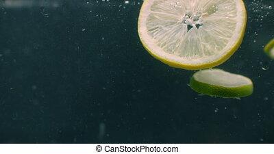 Limes splashing into water slow motion