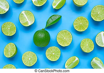 Limes with leaf on blue background. Top view