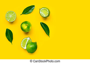Limes with leaves on yellow background.