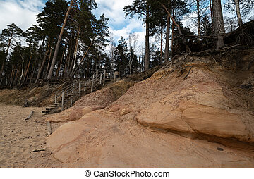 Limestone beach at the Baltic Sea, Latvia with beautiful sand pattern and vivid red and orange color - Veczemju Klintis Tourist writings on the walls and rocks and sand - 2019