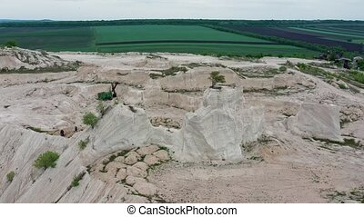 Aerial view to limestone Quarry near Fetesti village in Moldova, Eastern Europe, orbiting around lonely tree left at the top of rock
