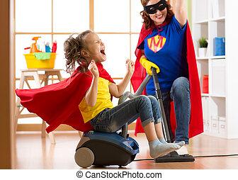limpador, mulher, filha, família, mãe, room., vestido, vácuo, middle-aged, floor., enquanto, limpeza, ter, criança, divertimento, usando, superheroes