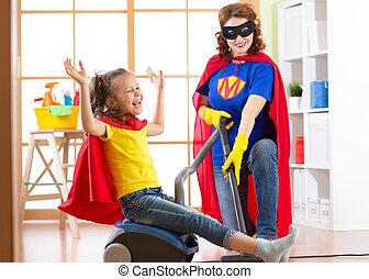 limpador, mulher, filha, família, room., vestido, mommy, vácuo, -, floor., enquanto, limpeza, ter, criança, divertimento, usando, superheroes, criança