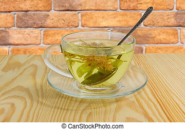 Linden flower tea in glass cup on wooden table