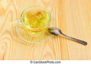Linden flower tea in transparent glass cup on wooden surface